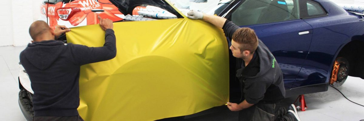 Two Vehiclewrappingcentre employees wrapping a car in yellow 3M vinyl