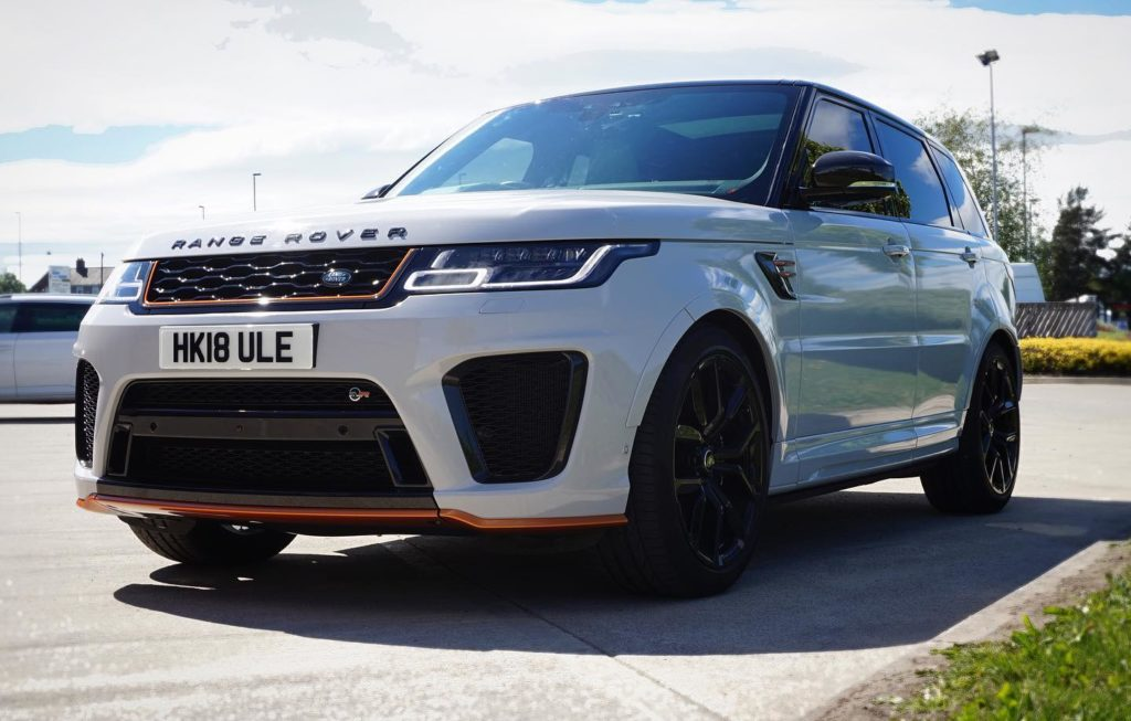 A picture of a Range Rover with beautiful new vinyl wrap in white with orange detailing.