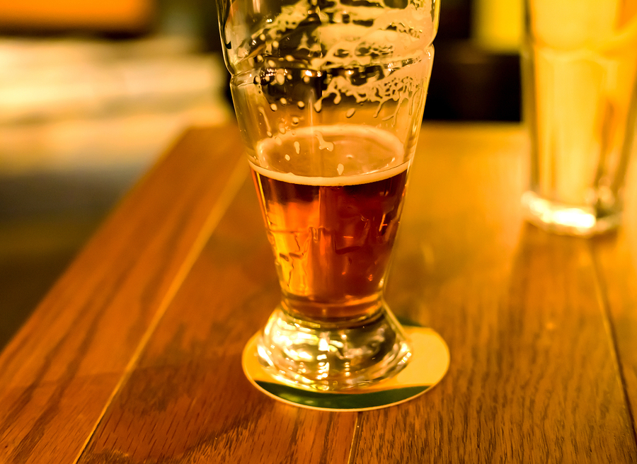 glass of foamy beer drunk delicious amber stands on a wooden table