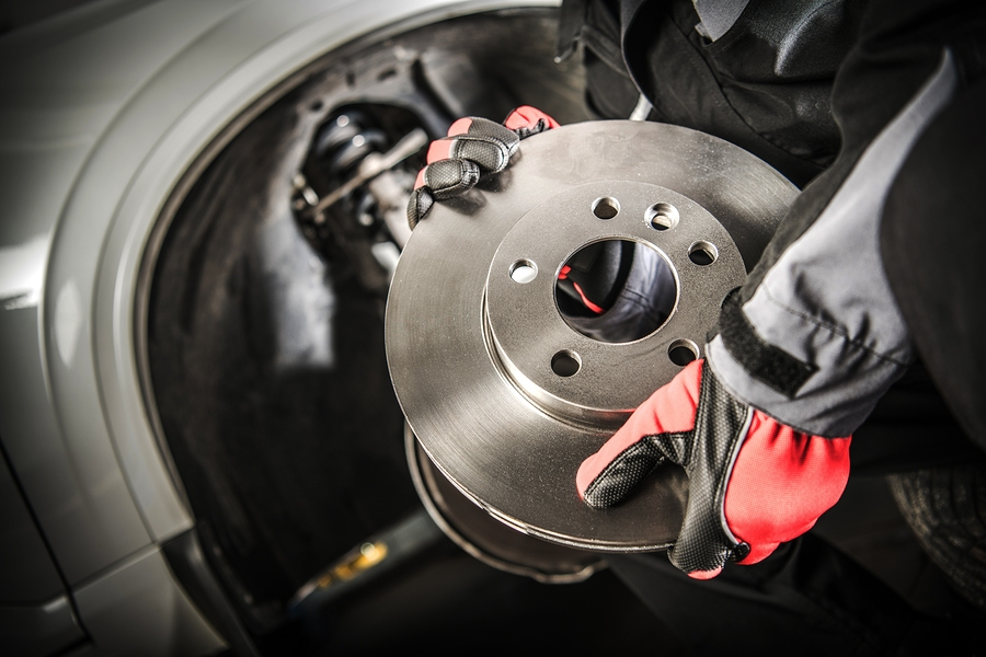 Car Mechanic With Modern Vehicle Brake Disc In Hands.