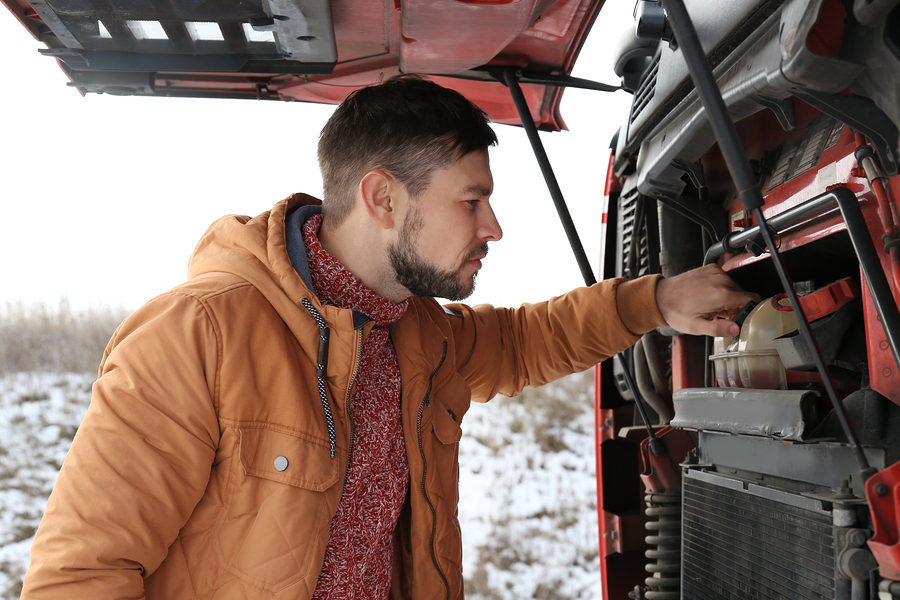 Handsome driver near truck with open hood outdoors