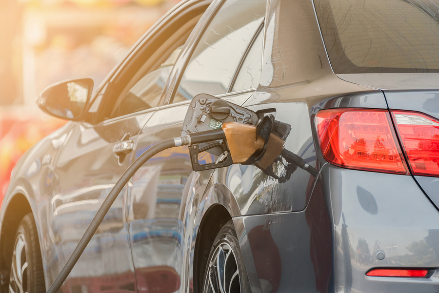 Small silver car refuelling at the gas station. Car refueling on petrol station. Fuel pump with gasoline. Car refueling on a petrol station. Car refueling on a petrol station closeup.