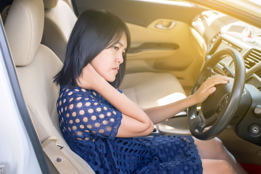 Asian woman tired have neck pain while driving a car
