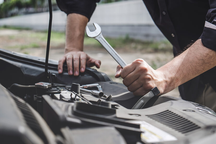 A man holding a wrench works on his car engine.
