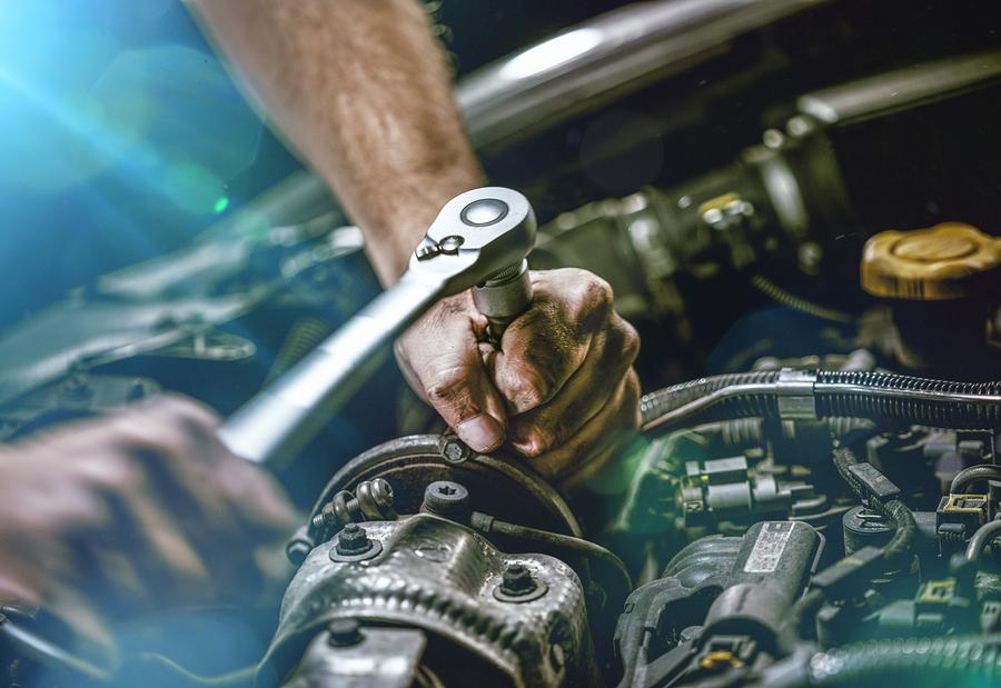Auto mechanic working on car engine.