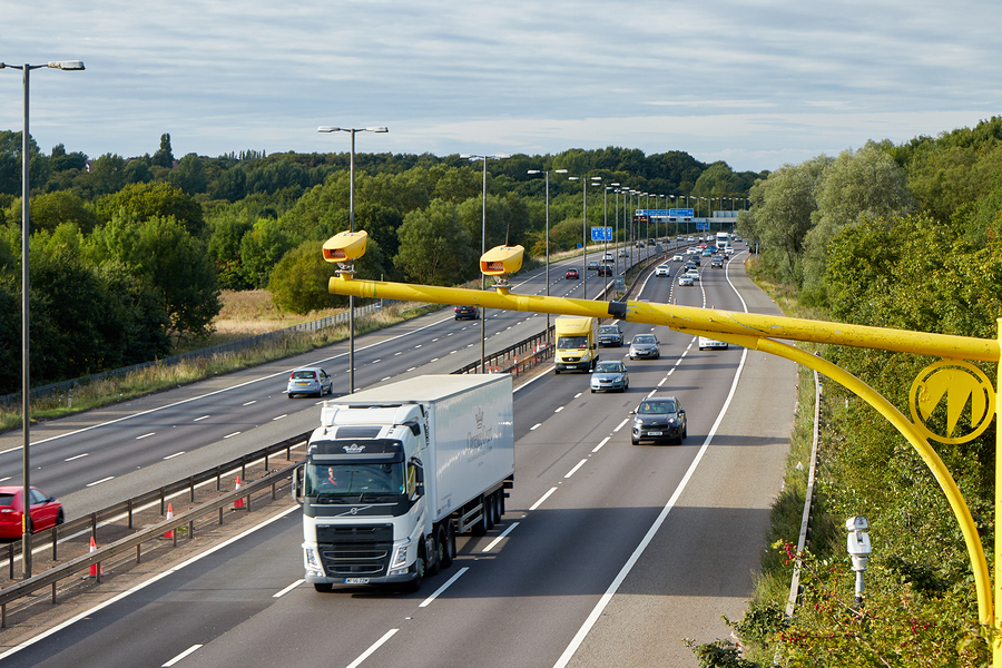 Cars driving on motorway under speed cameras