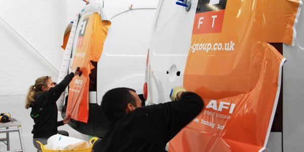 Orange and white vinyl wrapping process on AFI vans