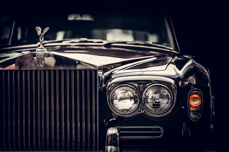 Rolls-Royce - classic British car on black background, close-up. Rolls-Royce remains a symbol of a luxurious car.