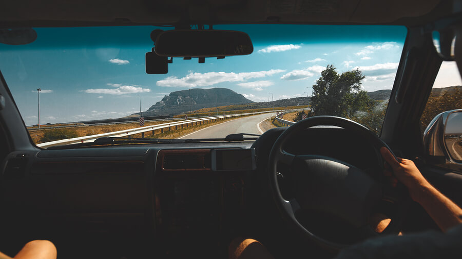 A picture of a couple driving in the summer. Point of View shot.