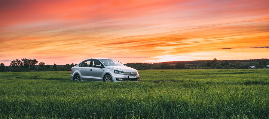 Volkswagen Polo Vento Car Sedan On Country Road In Spring Wheat Field Under Colorful Dramatic Sky At Sunset Or Sunrise Dawn. Concept Of Summer Trip Or Travel On VW Cars.