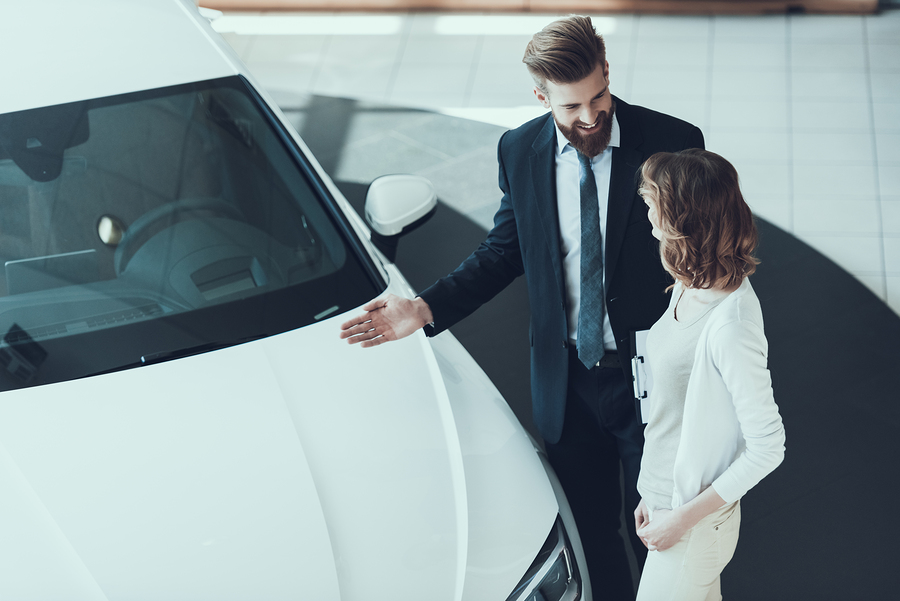 Car Salesman Showing Car to Woman in Showroom. Car Buying Deal. Beautiful Young Woman Talking to Caucasian Handsome Bearded Car Dealership Worker while Choosing Luxury White Car