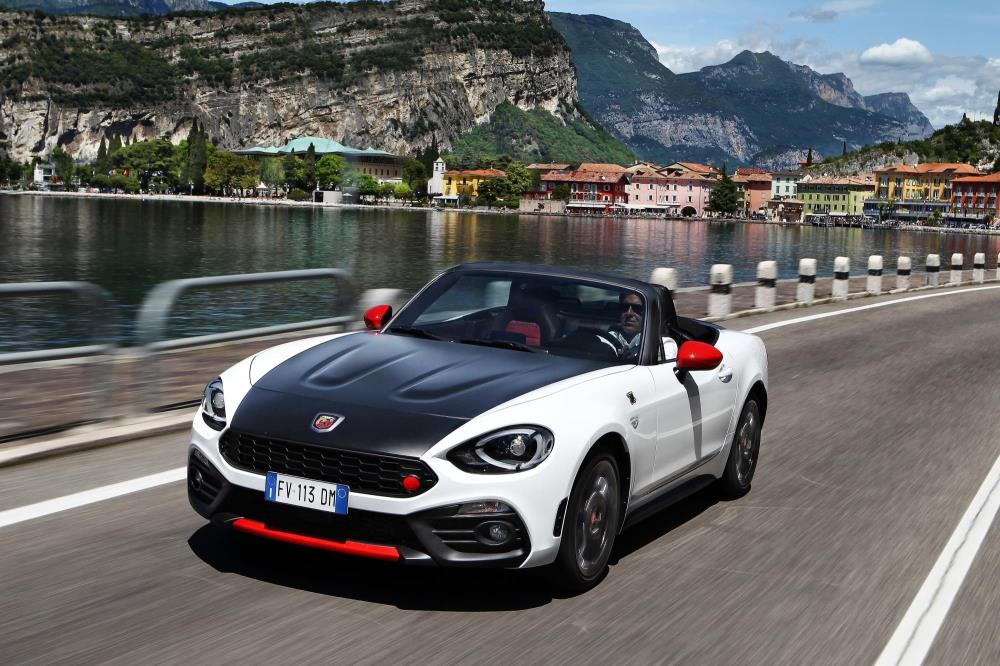 A wonderful Abarth 124 Spider driving along the road next to a lake.