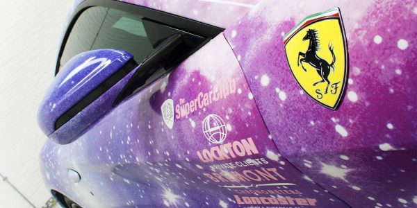 Close up of a digitally wrapped Ferrari themed as blue and purple cosmos with stars