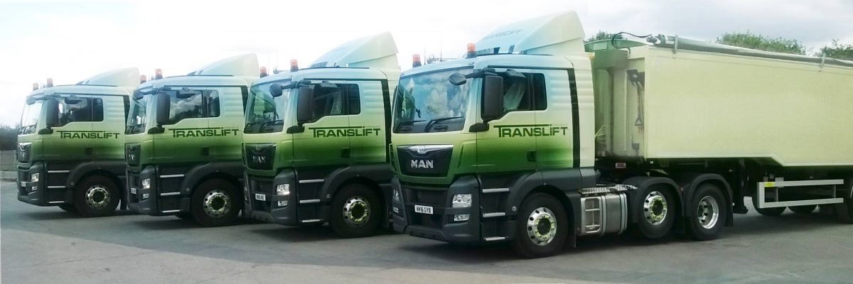 Four green vinyl wrapped trucks lined up side by side