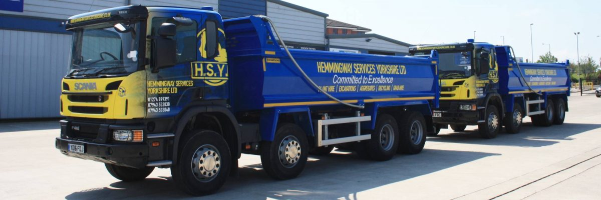 Two Hemmingway trucks lined up in blue and yellow vinyl wrap