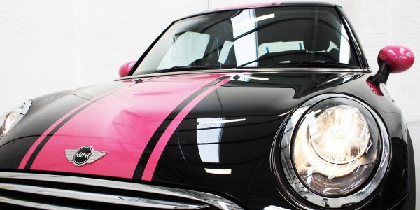 Mini cooper close up pink stripe of vinyl detailing on the shiny bonnet