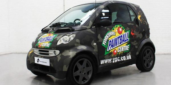 Black vehicle wrapped in paintball branding
