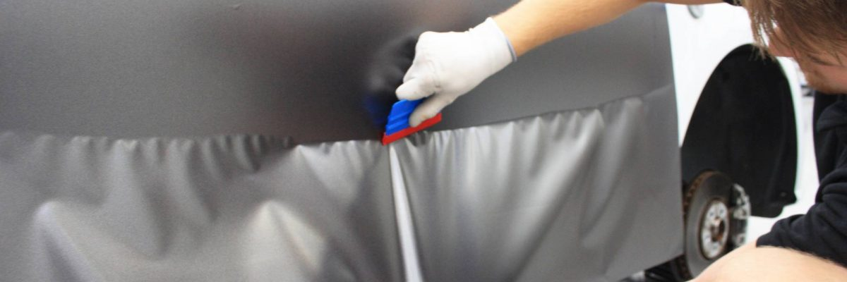 A sheet of smooth gray viny being smoothed out by an employee