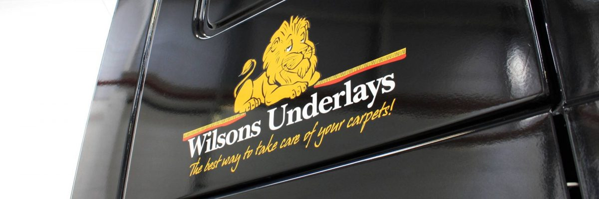 Wilsons underlays logo applied to side of a black vehicle
